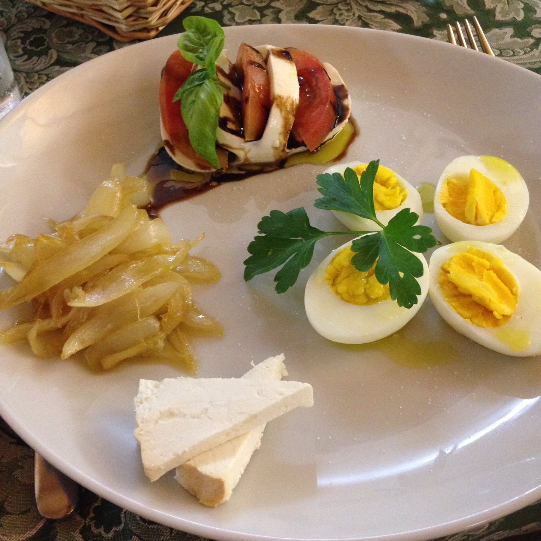 dinner plate with caprese salad, onions, and eggs