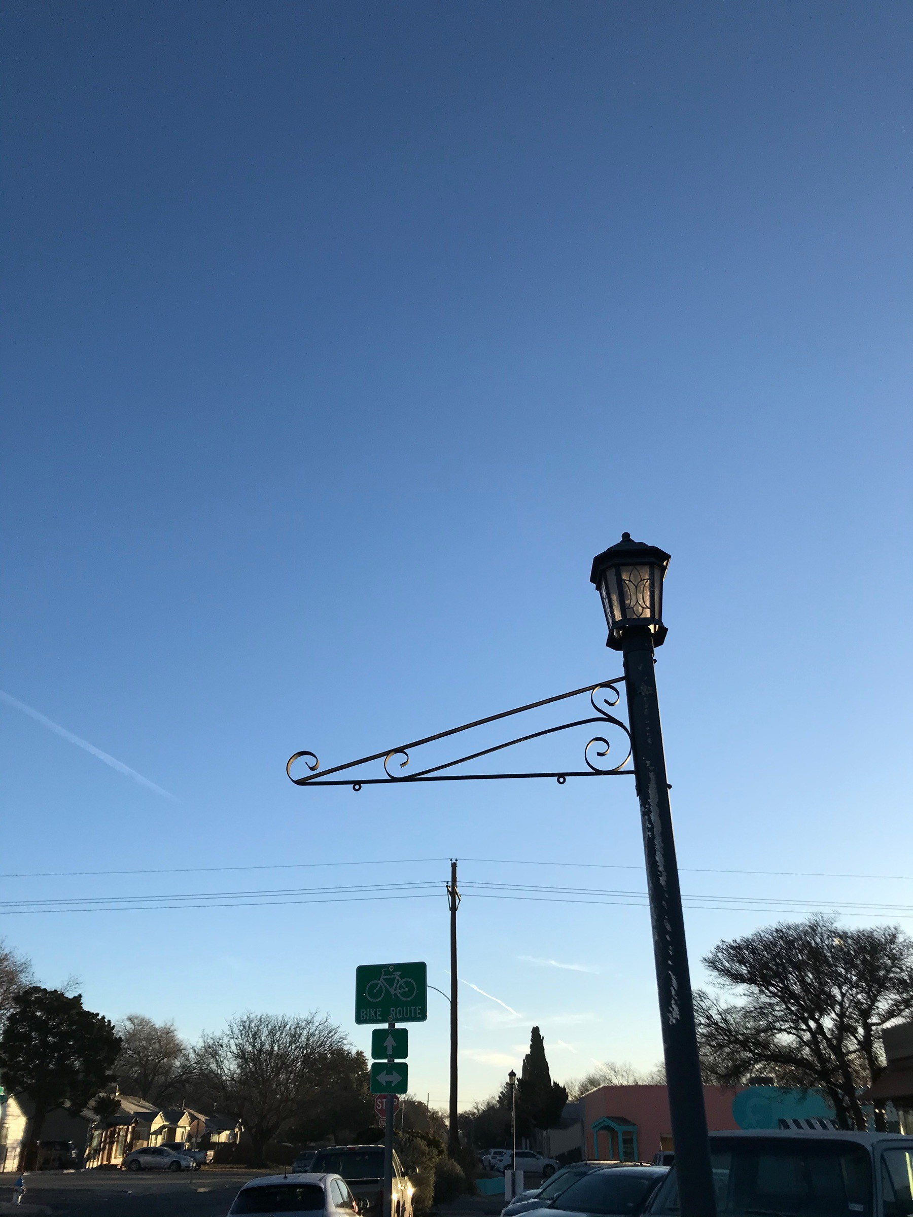 lamp post, power line, and contrail silhouetted against a brilliantly blue sky